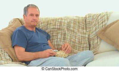 Mature man watching tv with popcorn