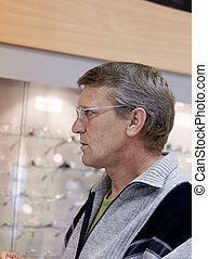 mature man wearing spectacles at a show-window with points