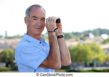 Mature man with binoculars.