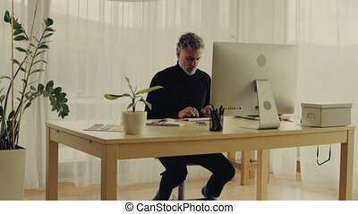 Mature man with computer working in home office.