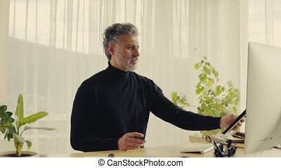 Mature man with computer working in home office. - Handsome...