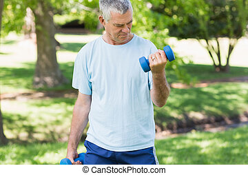 Mature man with dumbbells at park