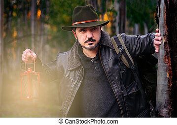 Mature man with hat and jacket with old lamp.
