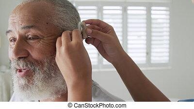 Mature man with hearing aid - Front view close up of a ...