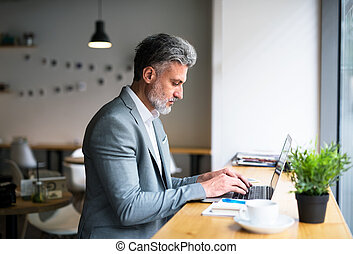 Mature man with laptop at the table in a cafe, working.