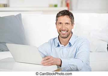 Portrait of happy mature man with laptop in house