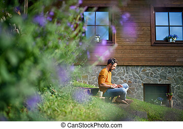 Mature man with laptop working outdoors in garden, home office concept.