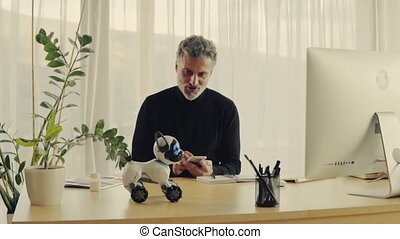 Mature man with robot smart dog in home office. - Handsome...