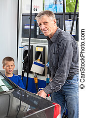 Mature man with son refueling vehicle with gasoline