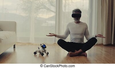Mature man with VR goggles and robot smart dog at home. -...