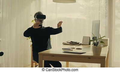 Mature man with VR goggles in home office. - Mature man with...