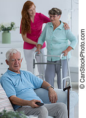 Mature man with walking stick sitting in chair