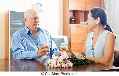 Mature man with woman having wine