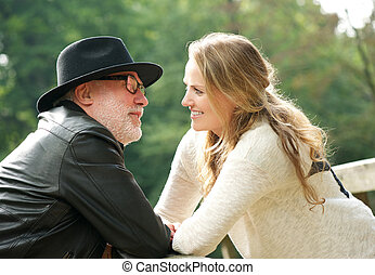 Mature man with young woman smiling at each other