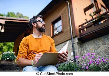 Mature man working outdoors in garden, green home office concept.