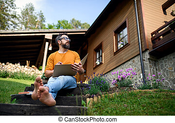 Mature man working outdoors in garden, home office concept.