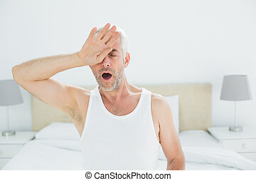 Mature man yawning in bed - Mature man yawning while sitting...