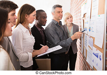 Manager Analyzing The Graph With His Colleague