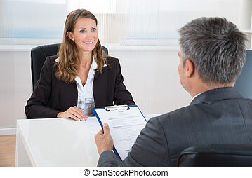 Manager Interviewing A Female Applicant - Mature Manager...