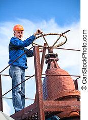Mature manual worker turning huge valve gate at factory