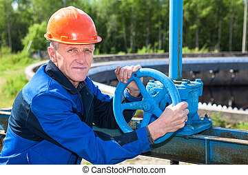 Mature manual worker turning stop-gate valve at factory