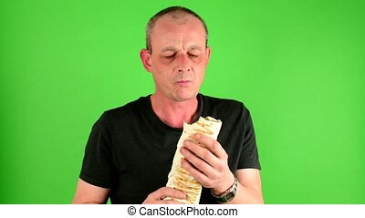 Mature mid aged man. Portrait of a mature man eats the fast food - kebab also called gyros in front of green screen.