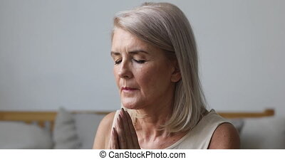 Mature middle aged woman praying with hope at home - ...