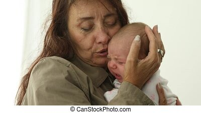 Mature mother holds and calms her new born baby girl. Face...