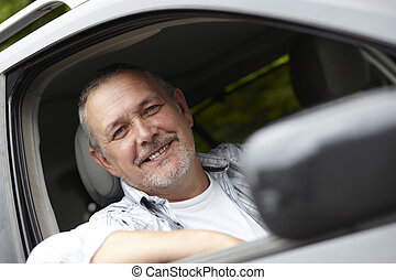 Mature Motorist Looking Out Of Car Window