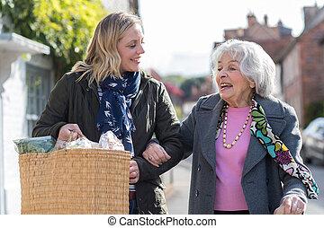Mature Neighbor Helping Senior Woman To Carry Shopping