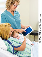 Mature nurse explaining reports on digital tablet to woman with newborn babygirl in hospital
