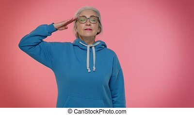 Yes sir. Subordinate, responsible serious mature old grandmother giving salute listening to order as if soldier, following discipline, obeying, expressing confidence. Senior woman on pink background