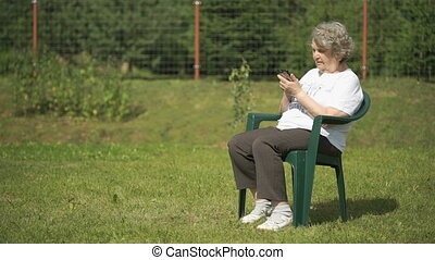 Mature old woman holds a smartphone outdoors - Mature old...