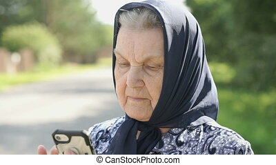 Mature old woman holds silver smartphone outdoors