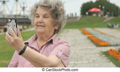 Mature old woman takes photos using a smart phone - Mature...