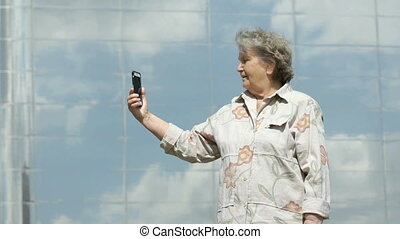 Mature old woman takes photos using a smart phone