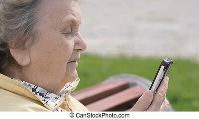 Mature old woman talking on mobile phone outdoors