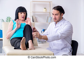 Mature old woman visiting doctor in hospital