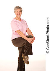 Mature older lady performing stretching exercises before gym workout