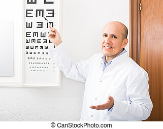 Mature optician showing symbols of Snellen chart in modern ...