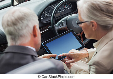 Mature partners working together on tablet in classy convertible on a bright day