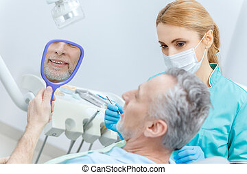 Mature patient looking at mirror while professional dentist checking teeth