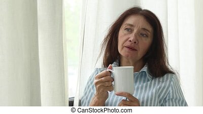 Mature pensive woman with coffee cup - Middle-aged woman...