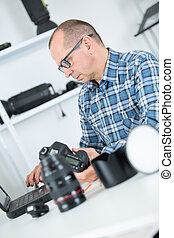 mature photographer cleaning lenses in his studio