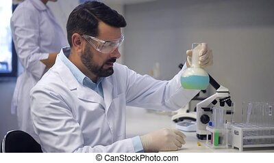 Mature researcher carrying out experiment in laboratory -...