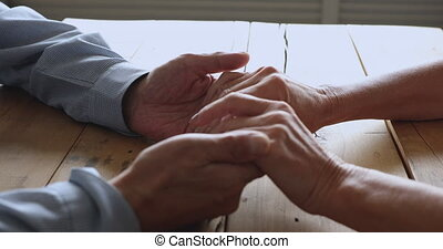 Mature retired family couple holding hands together on table.