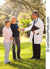 retirement village doctor greeting senior patient's daughter
