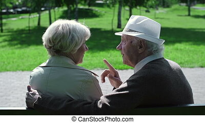 Mature Romance - Over shoulder shot of senior couple sitting...