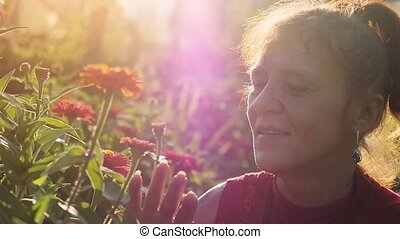 Mature romantic caucasian woman in age touches beautiful flowers in the park at sunset time with lense flare effects through the sun in slowmotion. Beauty, fashion and nature. 1920x1080