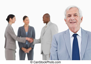 Mature salesman with trading partners behind him